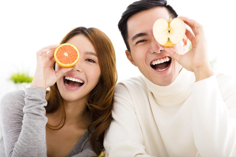 young happy couple holding fruits over their eyes