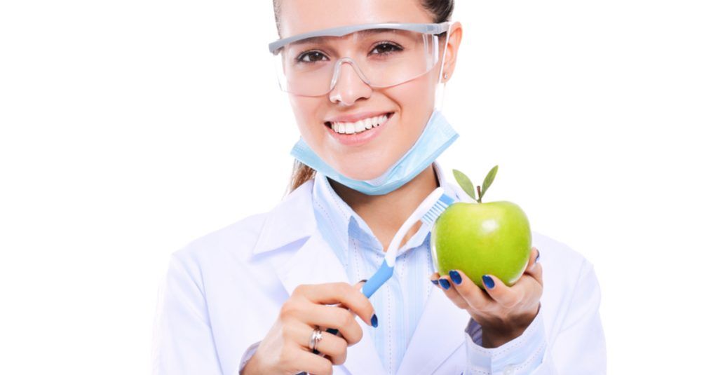 woman dentist holding a green apple and toothbrush