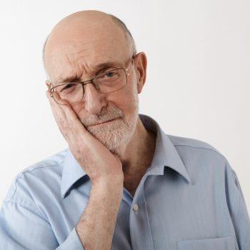 older man with dental implant pain