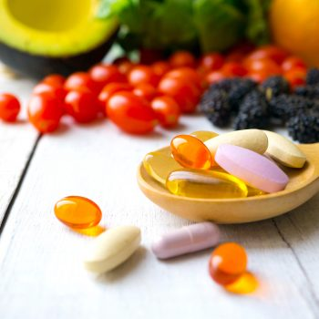 Pills and capsules in wooden spoon with fresh fruits.