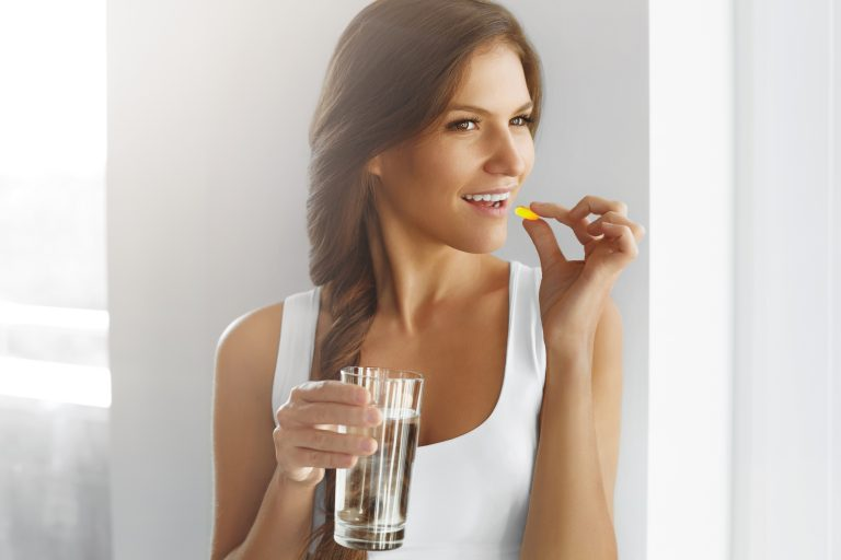 young woman holding a glass of water and taking her vitamins