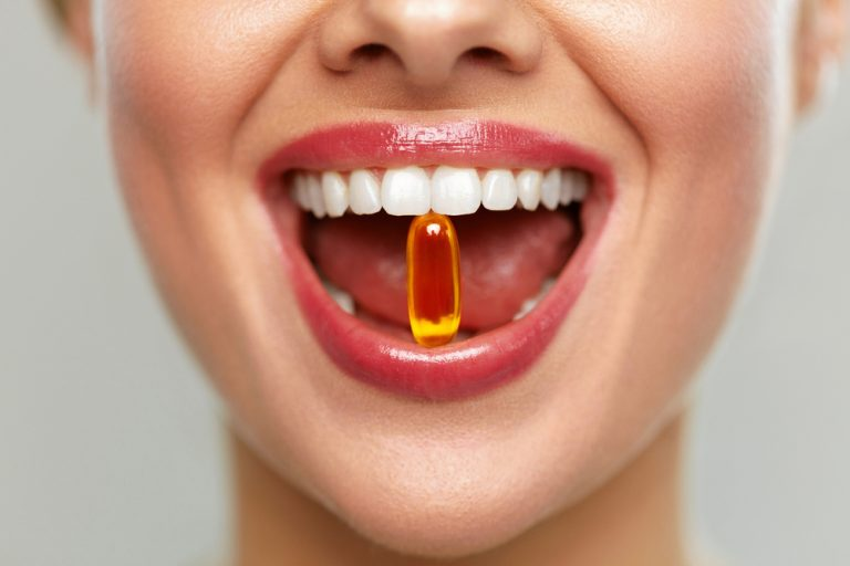 Close Up Of Beautiful Woman Opened Mouth Holding Fish Oil Pill In White Teeth
