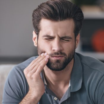 man holding his cheek from tooth pain