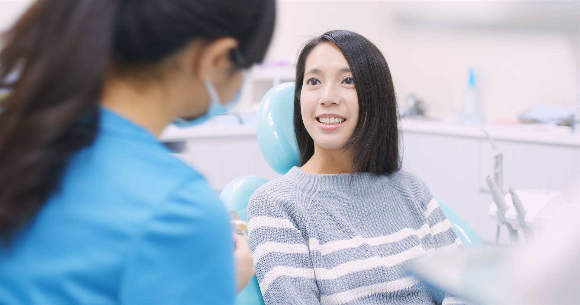 Woman in dental chair smiling and talking to a dental professional