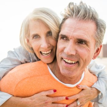 Older man in orange shirt smiling while his wife hugs him from behind smiling