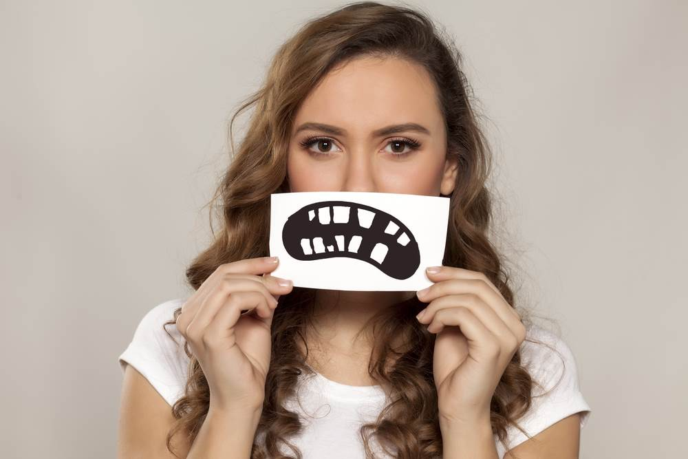 A young woman holding a illustration of bad teeth in front of her mouth.