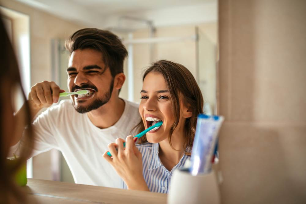 A young couple brushing their teeth together in front of the mirror.