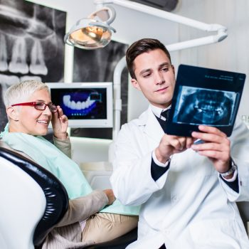 dentist showing x ray to smiling patient