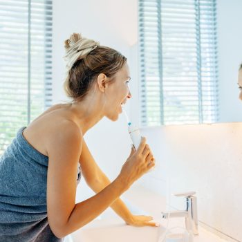 Woman at bathroom sink, looking in the mirror while using a water flosser