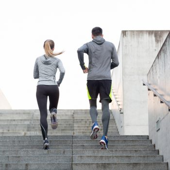 athletic couple running up stairs