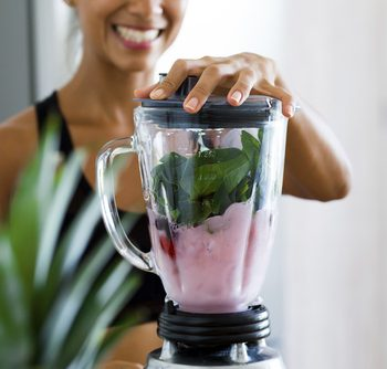 woman blending fruits and vegetables into smoothie