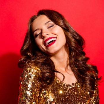 beautiful woman in a gold glittery shirt with a big white smile