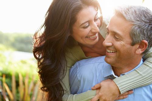middle aged Latino couple smiling and hugging