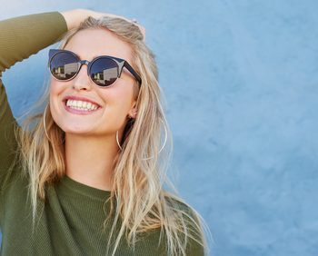 young woman in sunglasses smiling