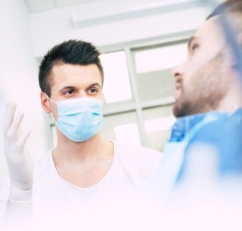 dentist having a discussion with a young male patient
