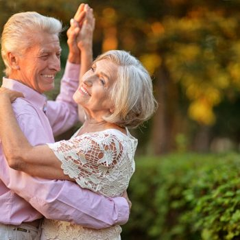 older couple dancing outside and smiling